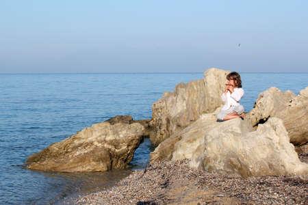 zampona: niña sentada en una roca junto al mar y jugando tubo de la cacerola