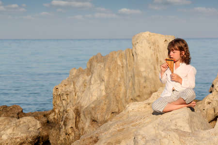 panpipe: little girl playing pan pipe by the sea