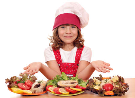 happy little girl cook with salmon seafood Standard-Bild