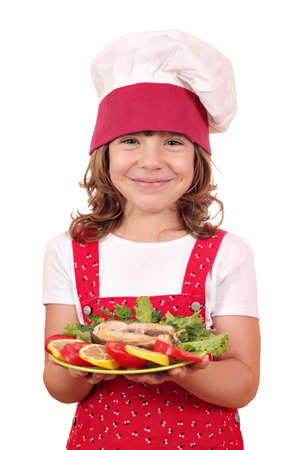 happy little girl cook holding dish with salmon seafood photo