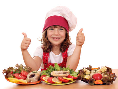 happy little girl cook with seafood and thumbs up Foto de archivo
