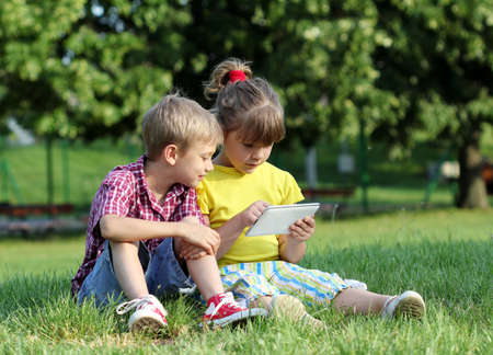little girl and boy with tablet in park