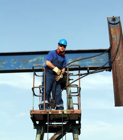 oil worker working on pump jack photo