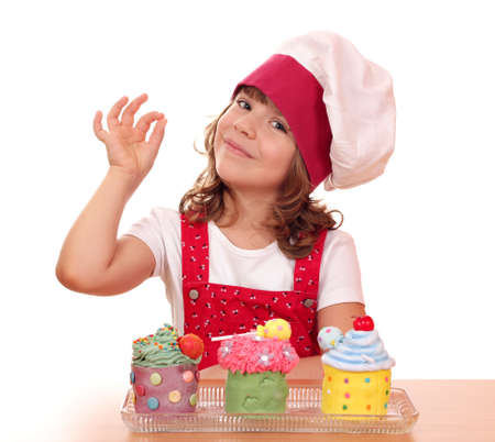 little girl cook with cupcakes and ok hand sign Foto de archivo