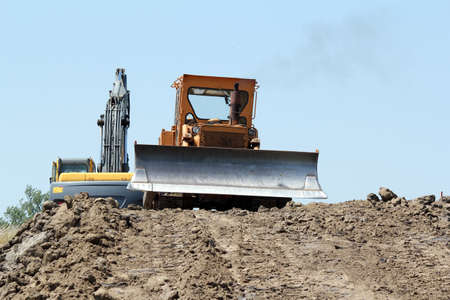 heavy bulldozer and excavator on road construction photo