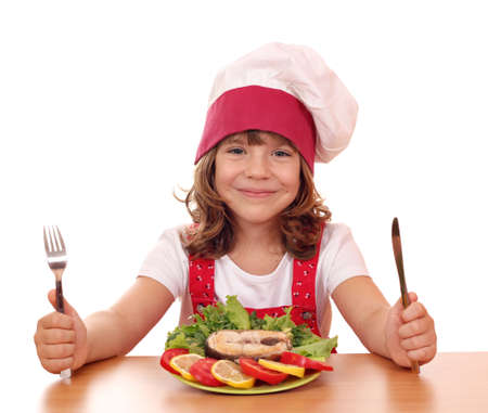 little girl cook with salmon seafood on table photo