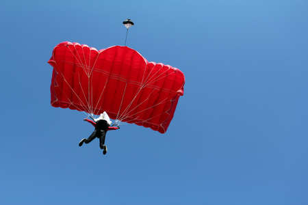 parachutist with red parachute on blue sky photo