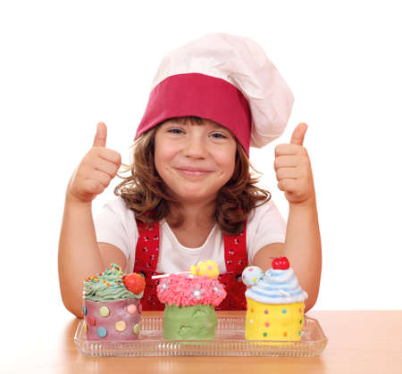 happy little girl cook with cupcakes and thumbs up photo