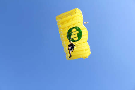 parachutist with yellow parachute on blue sky photo