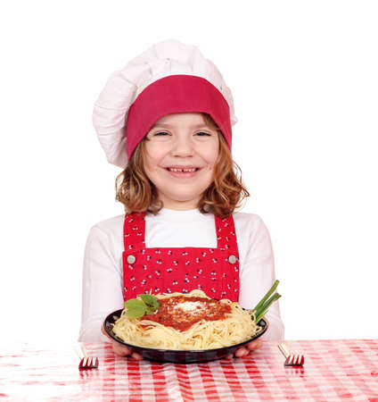 happy little girl cook with spaghetti on table photo