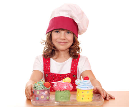 beautiful little girl cook with cupcakes photo