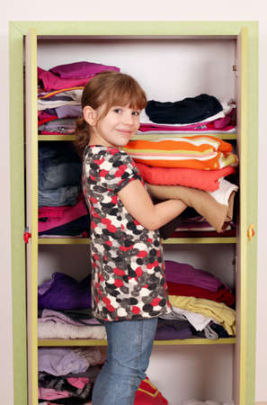 little girl girl agrees clothes in a closet  photo