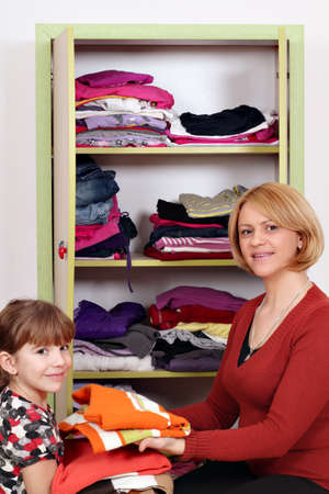 agrees: mother and daughter agrees clothes in a closet  Stock Photo