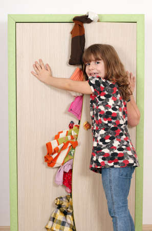upset little girl trying to close the closet  photo