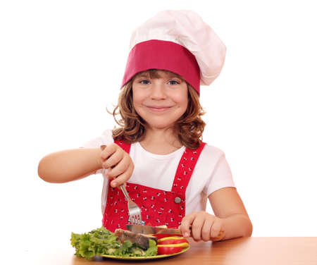 happy little girl cook eat salmon seafood photo