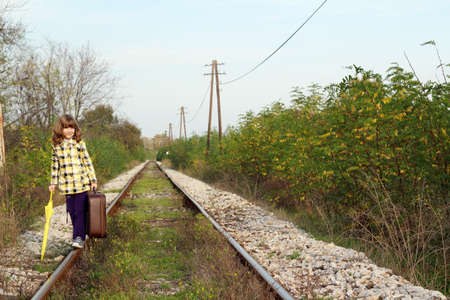 beautiful little girl with suitcase on railroad