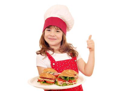 Niña feliz cocinar con sándwiches y el pulgar hacia arriba Foto de archivo - 25835652