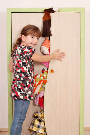 panic little girl trying to close the closet  photo