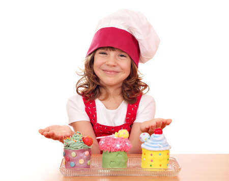 happy little girl cook with sweet cupcakes photo