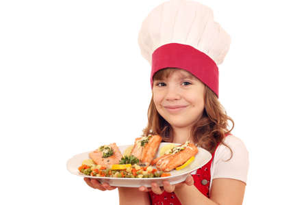 happy little girl cook with salmon and vegetables on dish photo