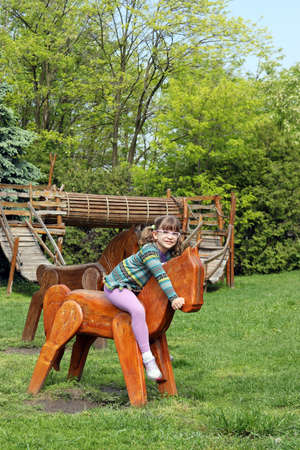 happy little girl riding wooden horse on playground photo