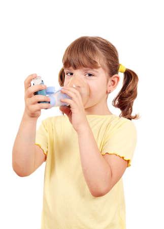inhale: little girl using an asthma inhaler