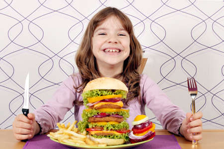 happy little girl with big hamburger on table photo