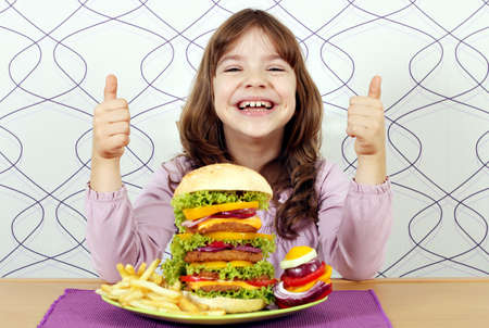 happy little girl with big hamburger and thumbs up photo