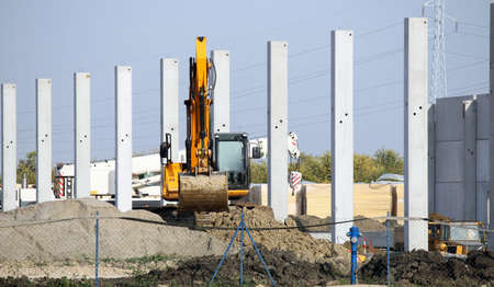 new building construction: new factory construction site with excavator Stock Photo
