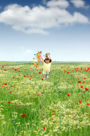 colorful flowers: happy little girl running in the spring meadow