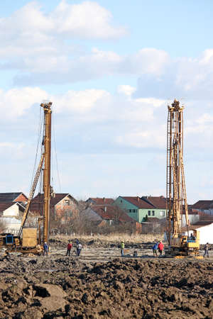 workers and hydraulic drilling machines on construction site