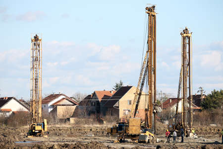 construction site with workers and three hydraulic drilling machines photo