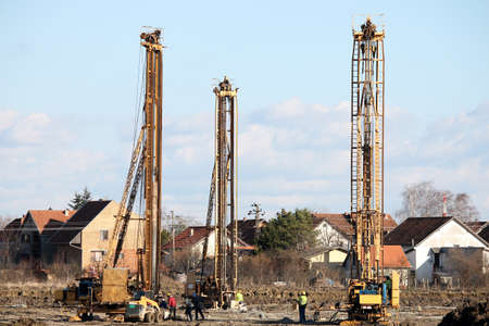 three hydraulic drilling machines and workers on construction site photo