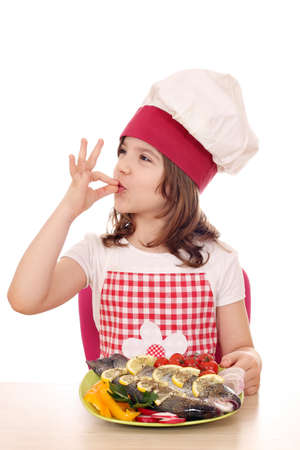 food: little girl cook with prepared trout on plate