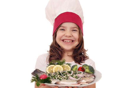 eating salad: happy little girl cook with prepared trout fish on plate