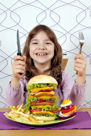 happy little girl with big hamburger ready for lunch photo