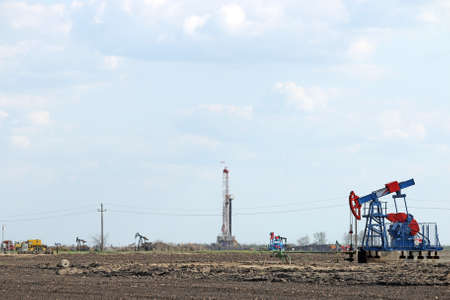 jacks: hot day on oilfield with pump jacks and drilling rig
