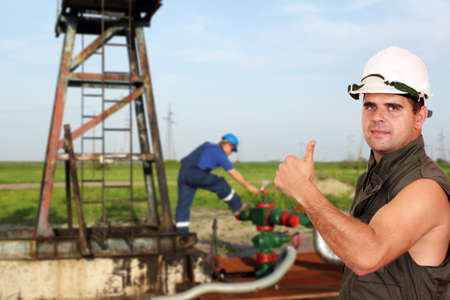 oil worker: oil worker with thumb up on oilfield