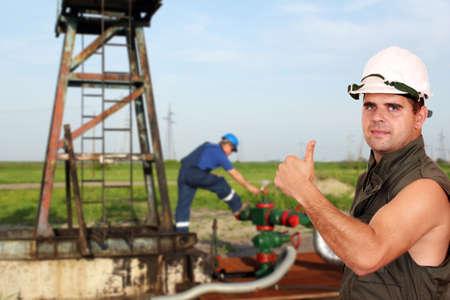 oil worker: trabajador petrolero con el pulgar para arriba en campo petrolero