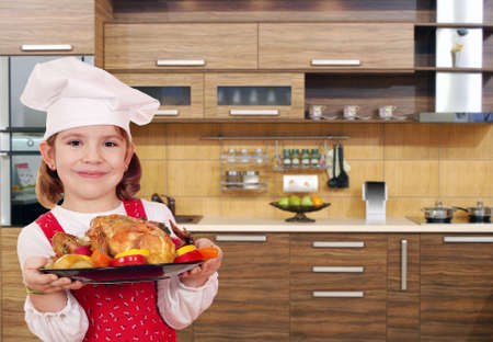 whole chicken: little girl cook with chicken in kitchen Stock Photo