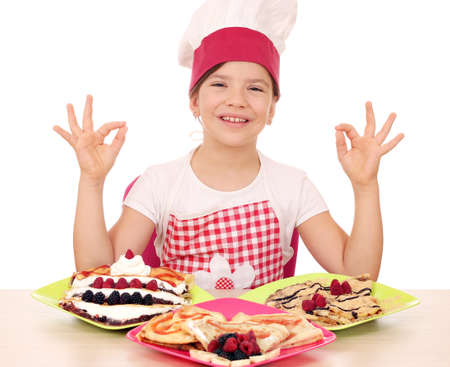 ok hand: happy little girl cook with delicious crepes on table and ok hand sign