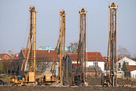 piling: four powerful hydraulic drilling machines on construction site Stock Photo