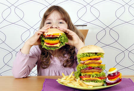hungry children: hungry little girl eating a big hamburger