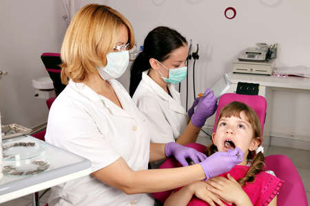 female dentist nurse and little girl patient photo