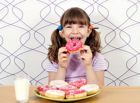 sugar: happy little girl eating donuts Stock Photo