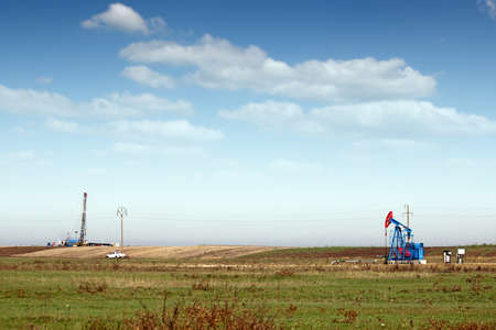 a field: oil pump jack and land drilling rig on field