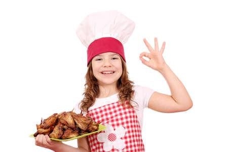 alitas de pollo: ni�a feliz cocinar con alitas de pollo asadas y muestra de la mano ok Foto de archivo