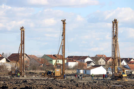 construction site with three hydraulic drilling machines and workers