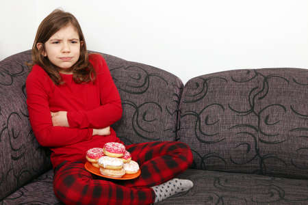 ate: little girl stomach ache because he ate a lot of donuts