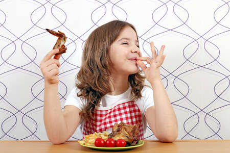 aliments droles: petite fille heureuse avec des ailes de poulet et signe de la main ok Banque d'images